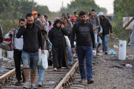 People walk along the railway tracks that connect Horgos and Szeged near the Hungary-Serbia border near Roszke, 180 km southeast from Budapest, Hungary, Tuesday, Sept, 8, 2015. (Zoltan Gergely Kelemen/MTI via AP)